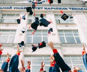 Studierende schmeißen ihre Abschlusshüte in die Luft